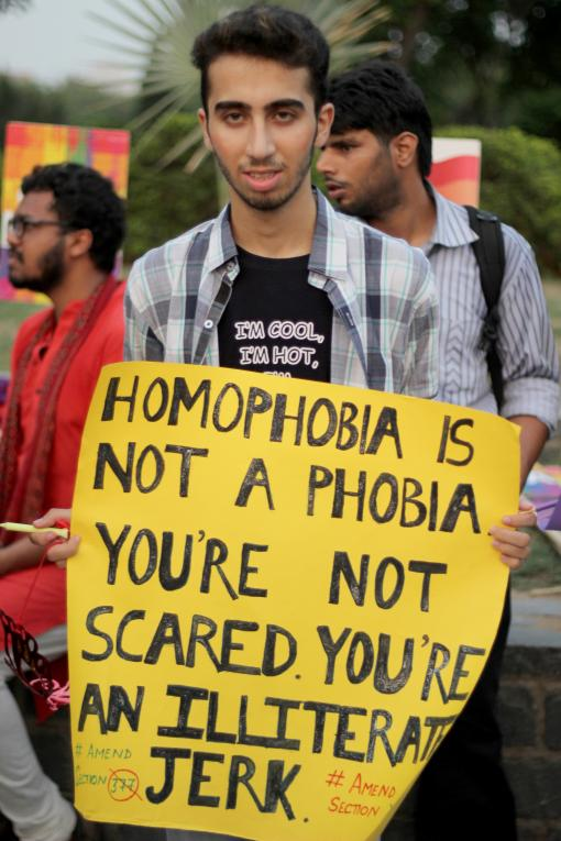 Young man holds a placard; Homophobia is not a phobia, you're not scared, you're an illiterate jerk.
