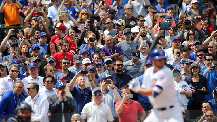 Baseball fans take photos and videos as Chicago Cubs infielder Kris Bryant hits.