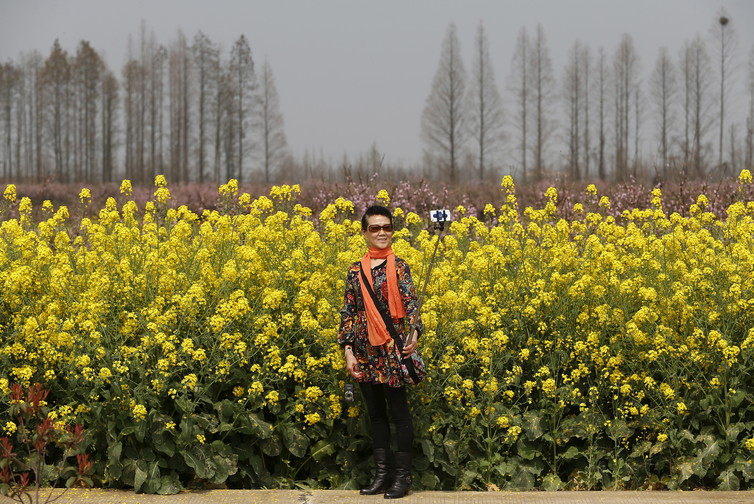 A woman uses a selfie stick in front of a field on the outskirts of Wuhan, China. Image source : Darley Shen/Reuters