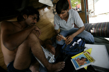 A volunteer demonstrates how to use a condom to a trucker. Photo credit: Brent Stirton/Getty Images for the GBC