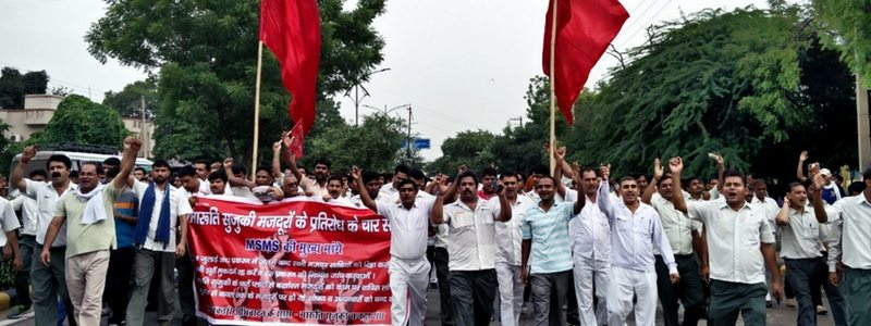 Group of workers holding banners and flags marching down a road. Photo credit: Abhishek Jha