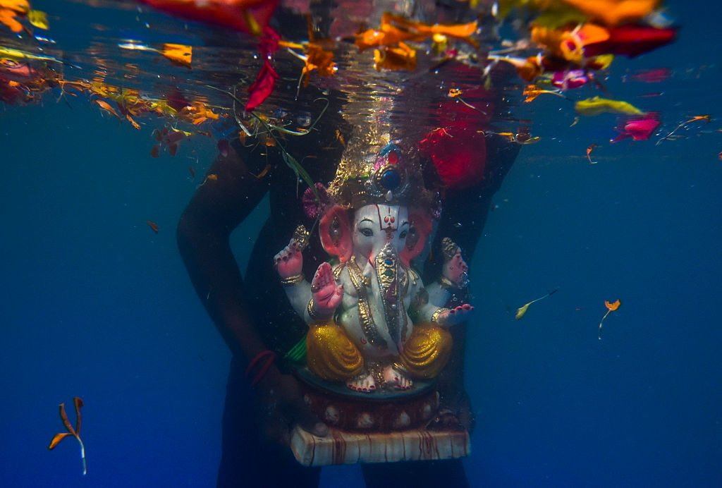 MUMBAI, INDIA - SEPTEMBER 6: An idol of elephant-headed Hindu God Ganesha floats after it was immersed in an artificial pond during 1 & 1/2 day of Ganesha Visarjan at Sion on September 6, 2016 in Mumbai, India. Ganesh Chaturthi is the festival celebrated by Hindus across the world in the honour of Lord. During the festival, local communities put up public pandals for mass worship, while families bring home small clay idols to pray. When the festivities end, the idols are immersed in large bodies of water. (Photo by Kunal Patil/Hindustan Times via Getty Images)