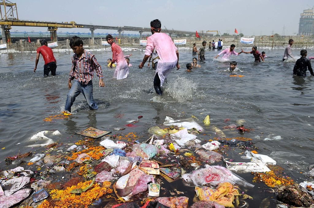 NOIDA, INDIA - SEPTEMBER 27: Waste floating after immersed Idols of Hindu Lord Ganesha in Yamuna River on the last day of the Ganesh Chaturthi festival at Okhla, on September 27, 2015 in Noida, India. Ganesh idols are taken through the streets in a procession for immersion in a river or a sea, symbolising a ritual seeing-off of his journey towards his abode, taking away with him the misfortunes of all mankind. It is said that after the Immersion of idol, Lord Ganesha residing in the idol, who listened to the prayers and request of his devotees for ten days, returns back to his heavenly abode. Despite recent orders from National Green Tribunal against putting non biodegradable material in water bodies, hundreds of plasters of Paris idols were immersed in water bodies across the city. (Photo by Sunil Ghosh/Hindustan Times via Getty Images)