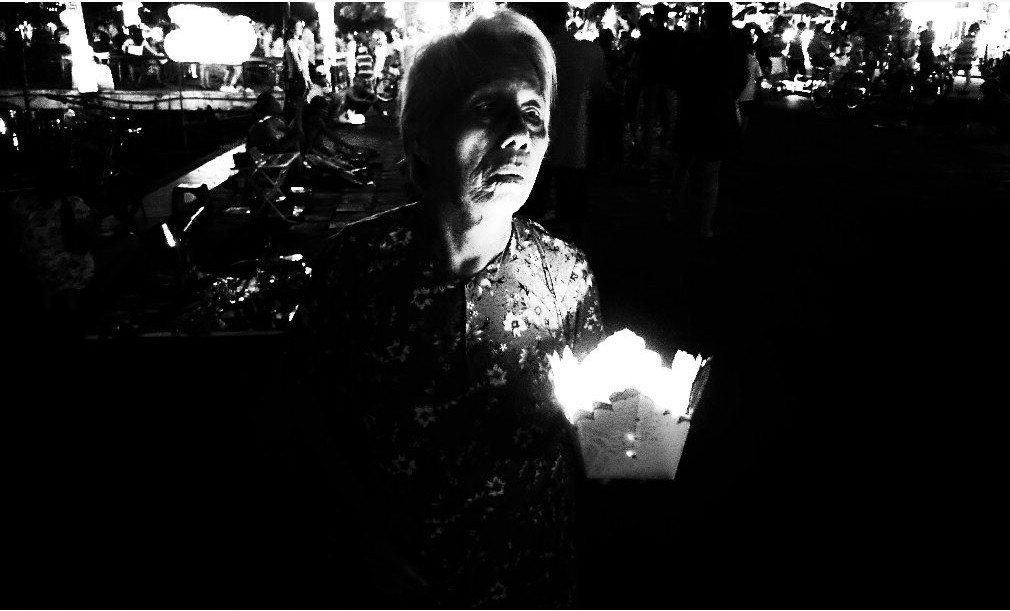 A woman peers across a lit lantern. Image Credit: Mekhala Dave