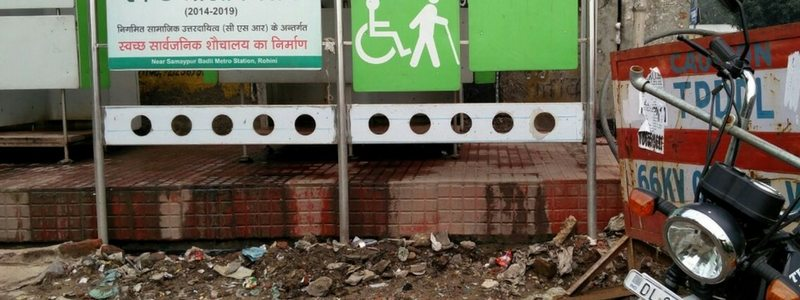 A toilet complex with urine flowing out of it and waste strewn around it.