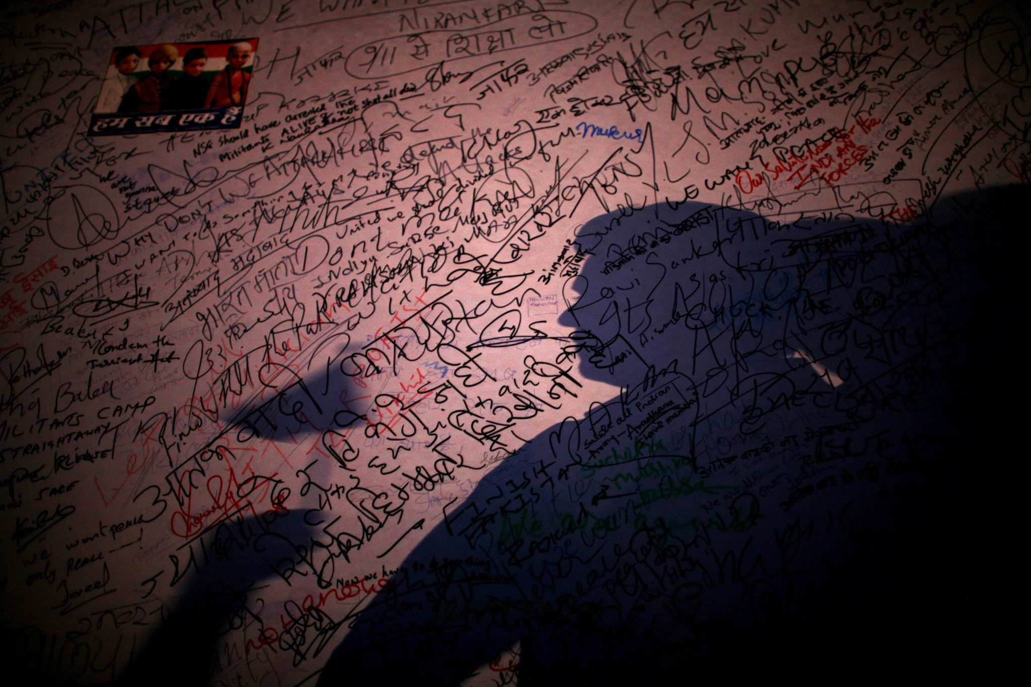 MUMBAI (BOMBAY), INDIA - DECEMBER 03: (ISRAEL OUT) An Indian man's silhouette is cast on a wall covered with signatures written in support of the victims of the recent terrorist attacks, as thousands of Mumbaikars take part in a mass demonstration march, near the Taj Mahal Palace & Tower Hotel, on December, 03, 2008 in Mumbai, India. Two bombs were discovered and defused earlier today by Mumbai police at a train station, the Chhatrapati Shivaji Terminus, which was one of the locations attacked by the terrorists. The attacks left almost 200 hundred dead and injured over 300 people. (Photo by Uriel Sinai/Getty Images)