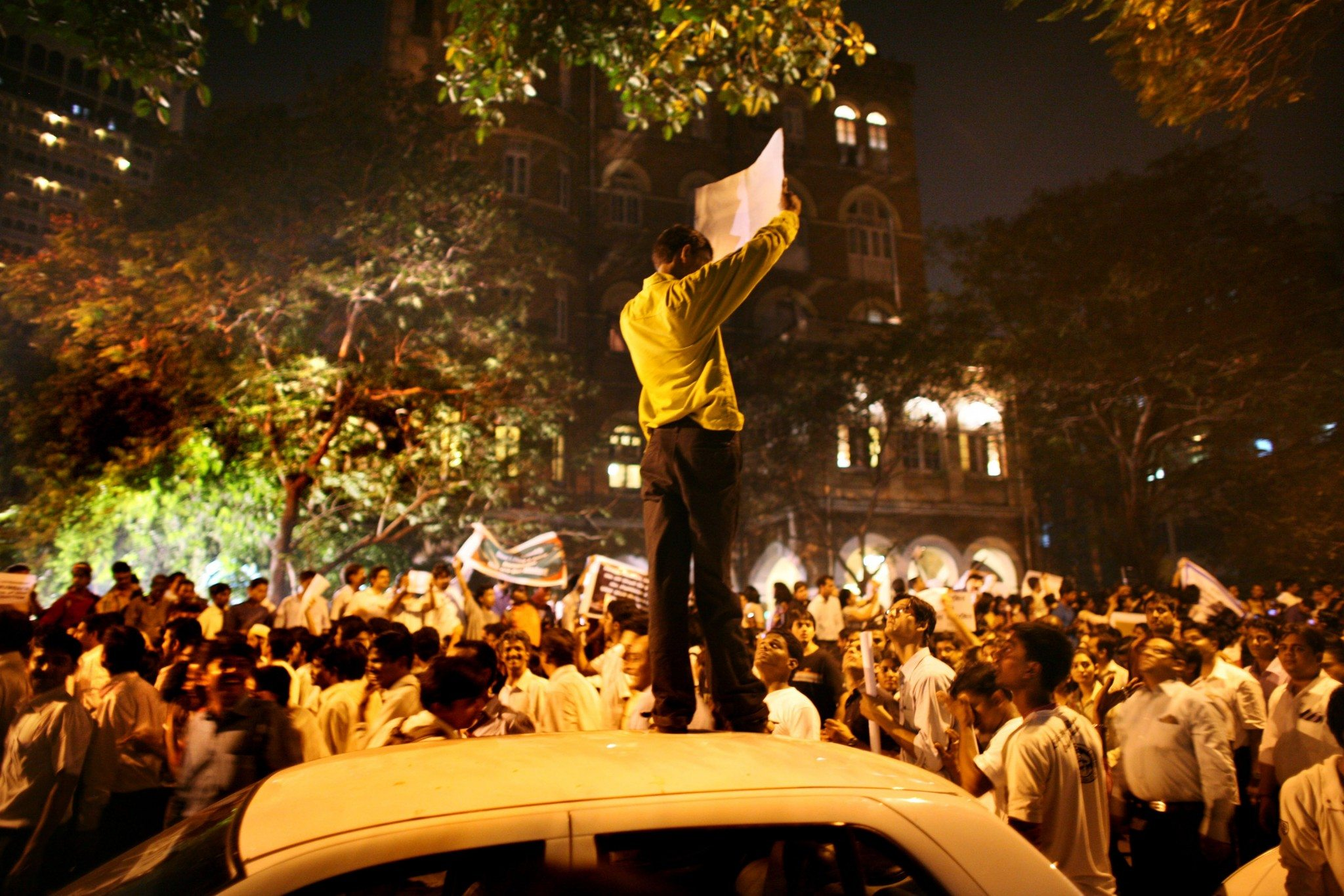 MUMBAI (BOMBAY), INDIA - DECEMBER 03: (ISRAEL OUT) An Indian man holds a sign as he stands on top of a car as thousands of Mumbaikars take part in a mass demonstration march following last weeks series of terrorist attacks on the city, near the Taj Mahal Palace & Tower Hotel, on December, 03, 2008 in Mumbai, India. Two bombs were discovered and defused earlier today by Mumbai police at a train station, the Chhatrapati Shivaji Terminus, which was one of the locations attacked by the terrorists. The attacks left almost 200 hundred dead and injured over 300 people. (Photo by Uriel Sinai/Getty Images)