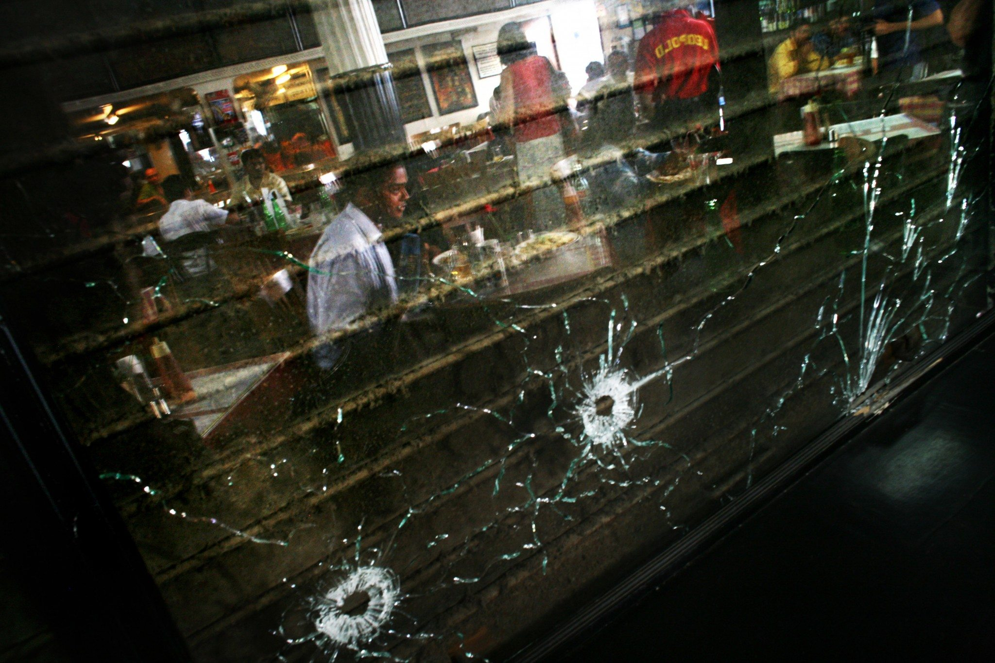 MUMBAI (BOMBAY), INDIA - DECEMBER 02: (ISRAEL OUT) A man is reflected in a window with bullet holes at the Leopold Cafe after it reopened on December, 02, 2008 in Mumbai, India. The Cafe was one of several locations targeted by multiple coordinated terrorist attacks on November 26. The attacks ended on November 29, with at least 173 people killed in the attacks. (Photo by Uriel Sinai/Getty Images)