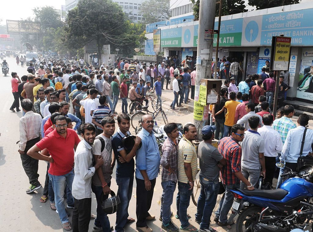 NOIDA, INDIA - NOVEMBER 13: People queued outside banks for the third day straight, trying to replace 500 and 1,000 rupee notes, on November 13, 2016 in Noida, India. Tempers frayed as hundreds of thousands of people queued for hours outside banks to swap 500 and 1,000 rupee bank notes after the notes were abolished earlier in the week. Nearly half of India's 2,02,000 ATMs were shut on Friday and those that operated quickly ran out of the new notes as scores of people descended upon them. (Photo by Sunil Ghosh/Hindustan Times via Getty Images)