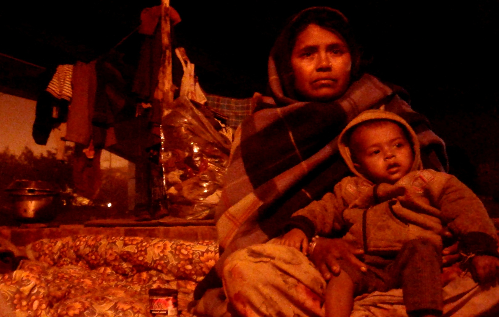 A homeless woman sitting with a child in her lap under a flyover at night.