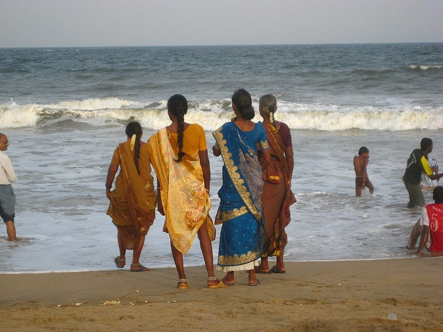 Women on a beach wearing different kinds of sarees