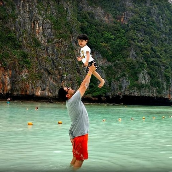 A man holds up a young child in a natural pool