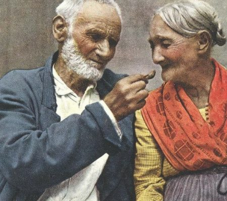 Old man feeding something to an old woman.