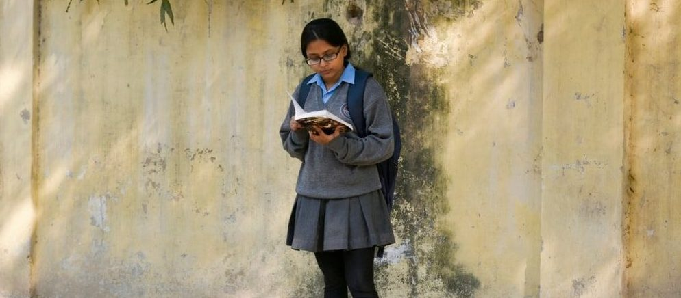 Girl studying while standing against a wall