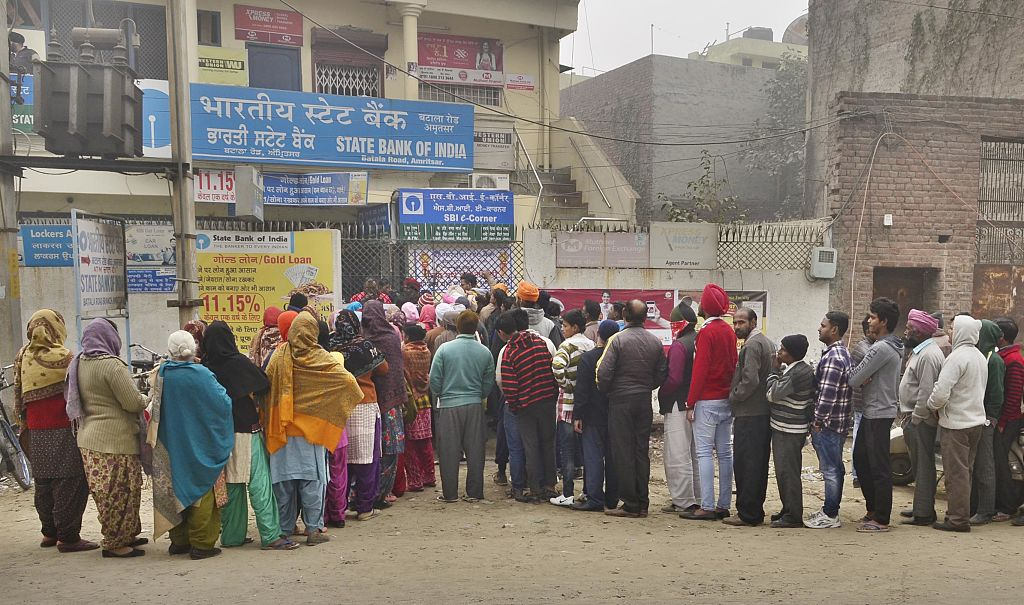 People stand in a queue outside a bank, post demonetisation