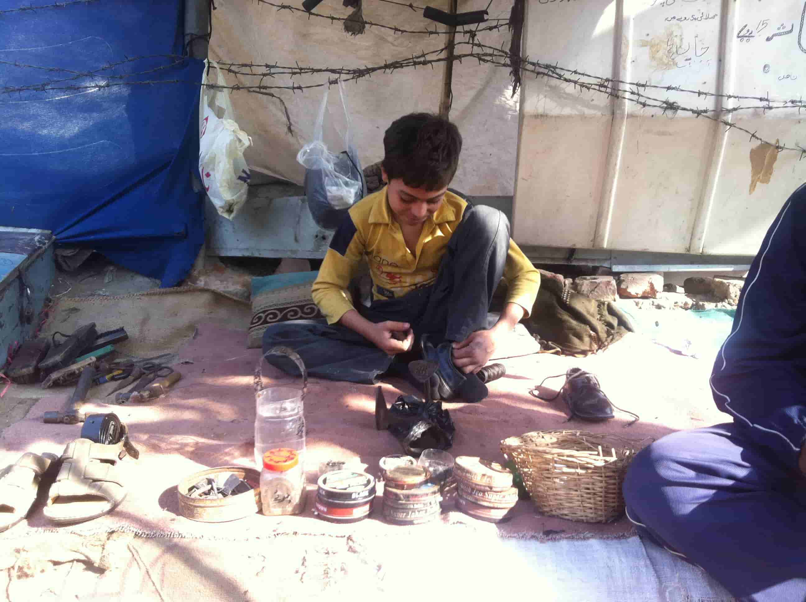 Child employed as a cobbler on the streets.