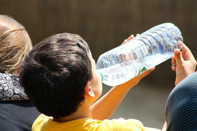 Boy drinking water from plastic bottle