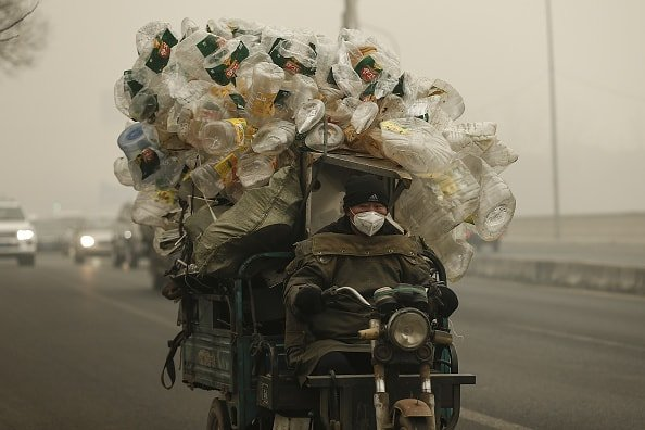 Chinese man taking plastic bottles for recycling