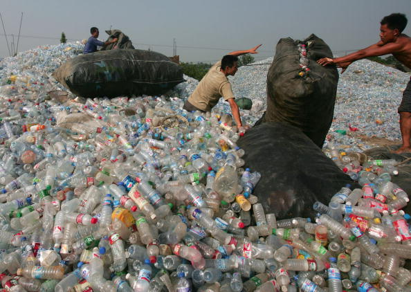 Workers Sort Out Plastic Bottles At Chinese Disposal Site.