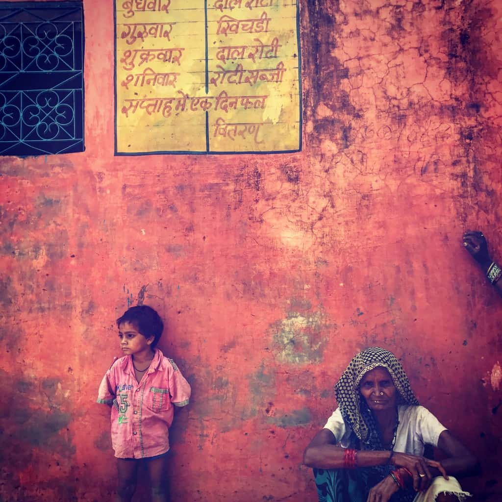 A child standing against a municipal school wall displaying the midday meal menu in a Rajasthan village.