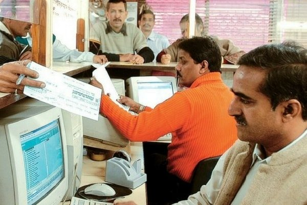 Two bank employees working on a computer in a cabin while customers stand across the counter holding their documents, cheques, etc.