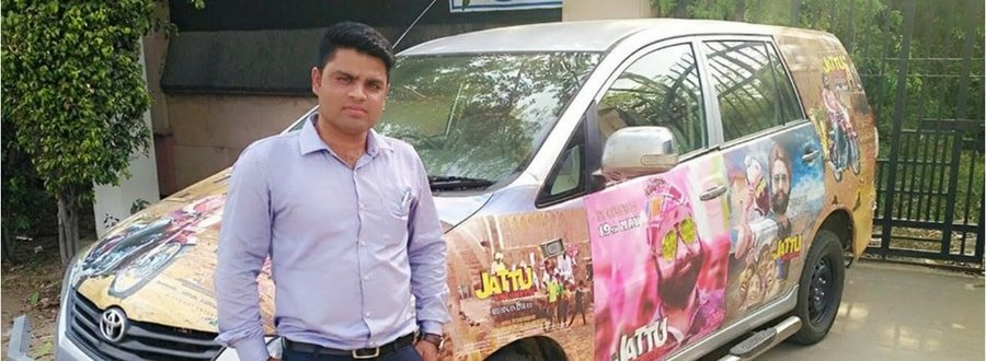 A young man starting in front of a toyota vehicle painted over with pictures of Ram Rahim.