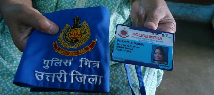 A woman holds an arm band and an ID-card identifying her as a Police Mitra.