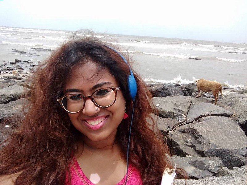 Description: In this picture of Durga, she is smiling, and wearing a pink top and blue headphones. In the background, there is the sea, and to her right, a small brown dog sniffs around the rocks.
