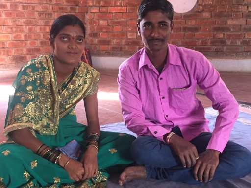 Sarika, wearing a green and gold outfit, and Sagar, dressed in a pink shirt, sit beside each other on the floor of their home, smiling. We see brick walls in the background.