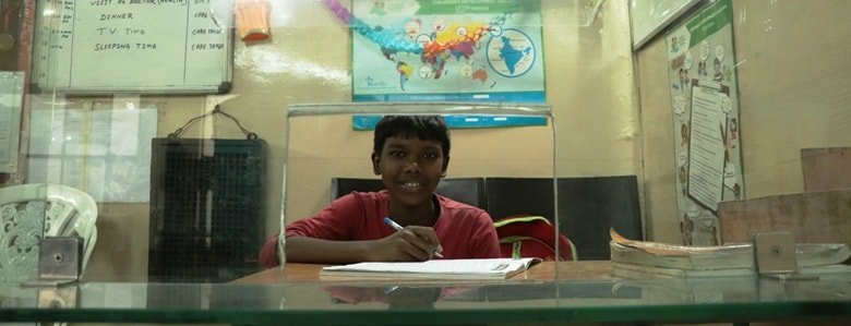 A child sitting behind a counter with a notebook and a pen.