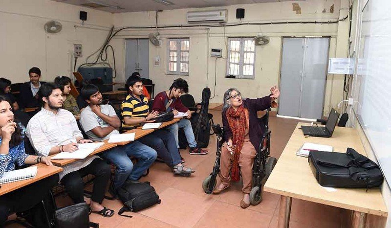 Anita Ghai is sitting on a wheelchair and speaking as well as gesturing towards a whiteboard as students listen to her inside a classroom. Credit: Aayush Goel/The Week