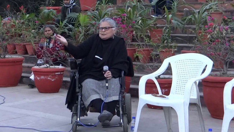 Anita Ghai, dressed in black and white, is holding a mic in one hand while gesturing with the other. She is seated on a wheelchair inside of a University campus. There are steps behind her, and people seated on some of them. Credit: YouTube screenshot.
