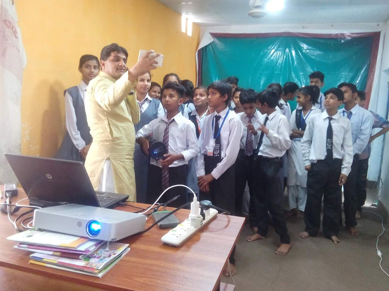 A photo of Raza in a classroom. He's taking a selfie with his students.