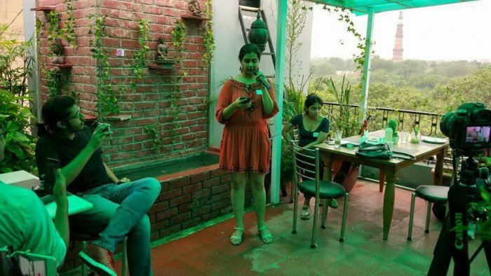 The setting is a cafe on a terrace, with leaves on the wall. A person in a red dress is speaking into a mic; a camera is recording this. There are two other people in the vicinity.