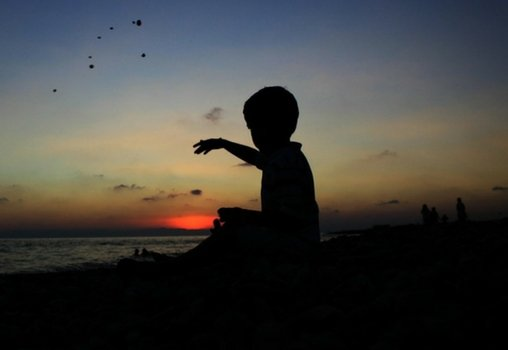 A silhouette of a child sitting on a beach with one arm raised towards the sea.