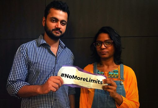 "a man and woman holding up a sanitary napkin with the message ""#NoMoreLimits"""