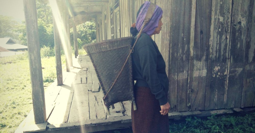 A woman, with a basket hanging from her head, heading out to work in Noney.