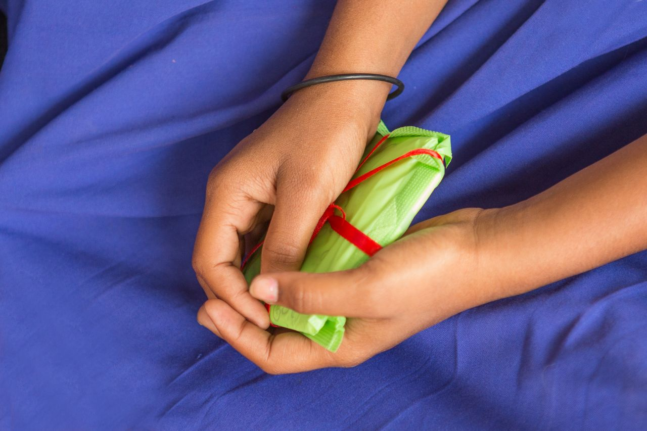 Two hands on a blue cloth background holding a green sanitary napkin tied with a red ribbon