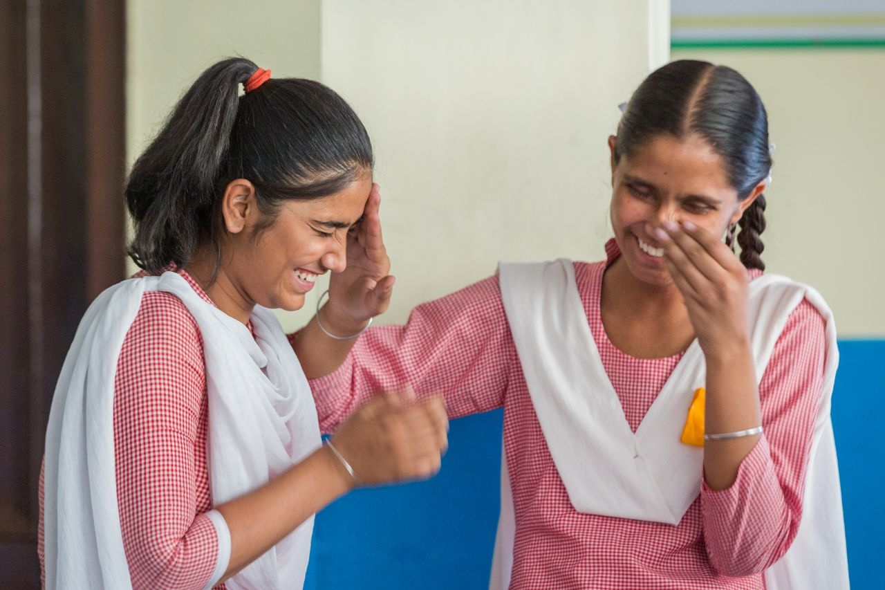 two Indian school girls in red and white uniforms laughing