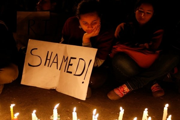 woman sitting for a protest with a placard saying 'Shamed'