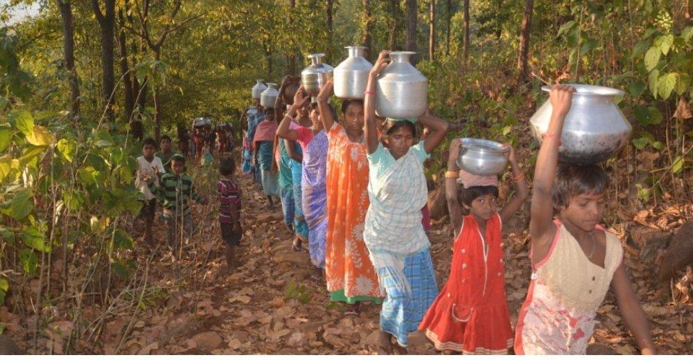 पहाड़ी जंगली रास्ते के ज़रिये डोभे से पानी भरकर घर जाती महिलाएं