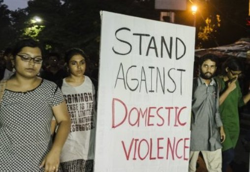 people at a protest with a banner thats says Stand Against Domestic Violence.