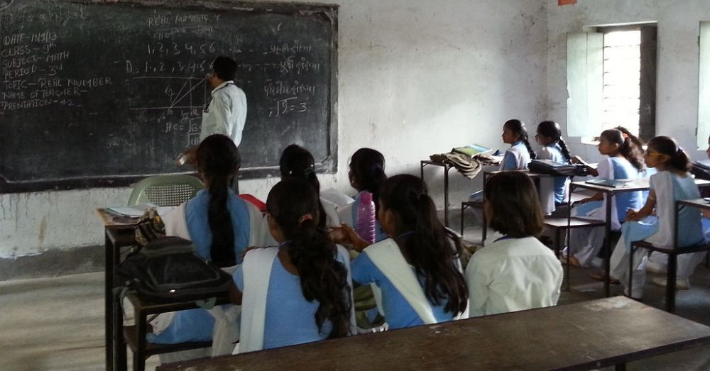 Girl students in a class sit facing a teacher who is writing on the backboard