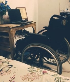 Image of an empty wheelchair in front of a desk that has a an open laptop with a blank screen on it. In the corner or the image a part of the bed is visible.