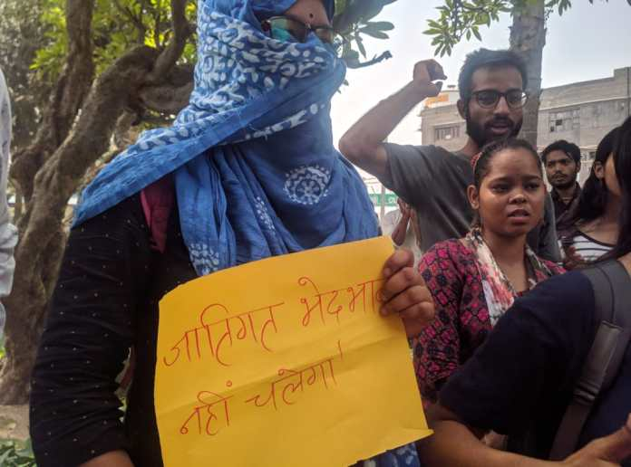 A student holding a sign during the sanitation workers' struggle in Ambedkar University, Delhi.