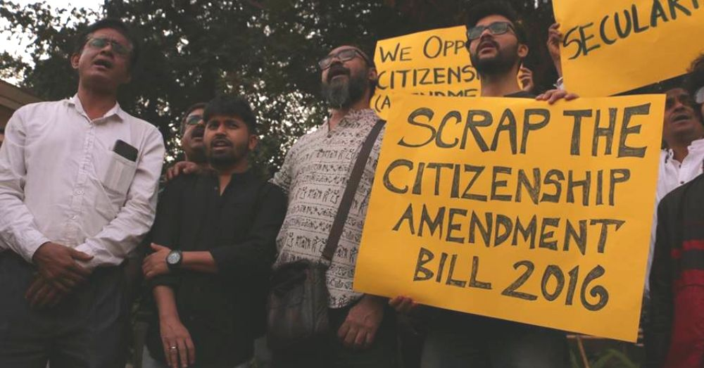 person holding a banner that says scrap the Citizenship Amendment Bill 2016.