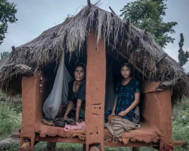 Two women sitting inside a cramped and dilapidated menstrual hut.