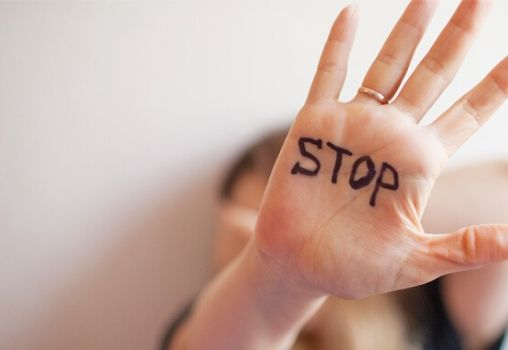 a woman saying stop to abuse and harassment