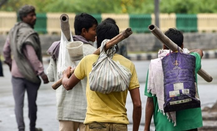 migrant labourer walking with their belongings