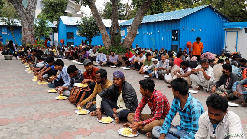 Migrant workers eating at a relief camp.